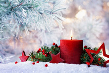 Christmas Or Advent Candle, Fir Branches, Berry And Red Stars In Snow Against Beautiful Winter Background. Holiday Card.