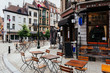 canvas print picture - Old street with tables of brasserie in center of Brussels, Belgium. Cozy cityscape of Brussels (Bruxelles). Architecture and landmarks of Brussels.