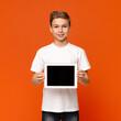 Leinwandbild Motiv Confident teen boy showing blank digital tablet