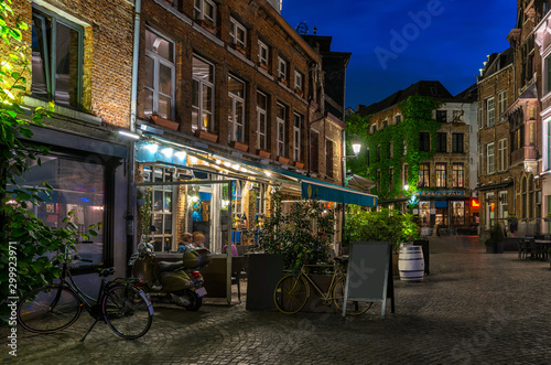 Spoed Foto op Canvas Antwerpen Old cozy narrow street with tables of restaurant in historic city center of Antwerpen (Antwerp), Belgium. Night cityscape of Antwerp. Architecture and landmark of Antwerpen