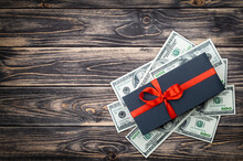 Black Gift Box With Bow With Dollars Banknotes On Wooden Backgroung. Top View