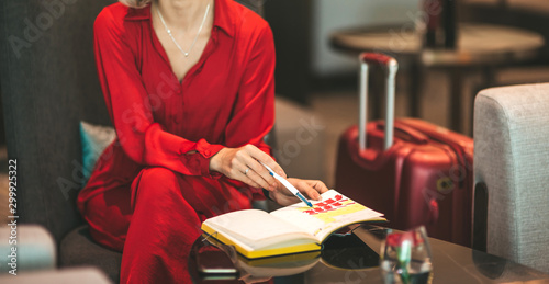 Fotografía  Cropped portrait of gorgeous lady with blonde hair wearing red jumpsuit, looking at notes in her notebook while sitting on the couch