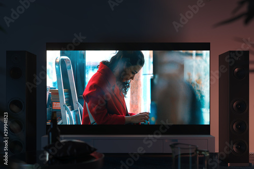 Photo  Big black tv set with film shot on white cupboard in modern interior, 3d rendering