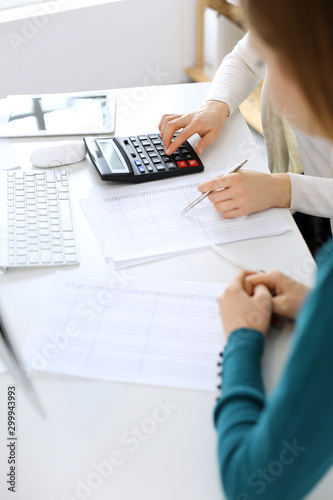 Accountant checking financial statement or counting by calculator income for tax form, hands close-up Canvas Print