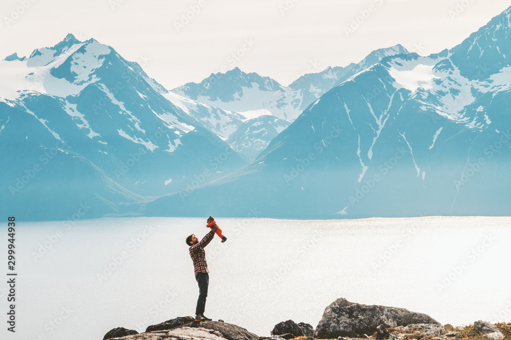 Fototapety, obrazy: Father holding up baby hiking in mountains travel family adventure lifestyle vacations dad with kid outdoor journey in Norway