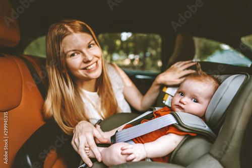 Fototapeta Mother putting baby in safety car seat happy family road trip vacations lifestyl