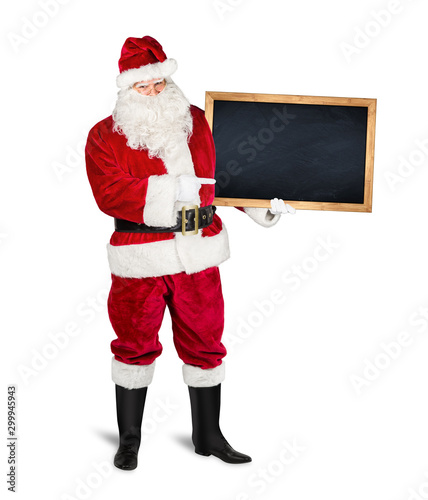classic traditional red santa claus holding empty wooden slate blackboard chalkboark pointing with finger on it. blank slate with copy space isolated white christmas advertising background - 299945943