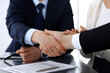 Business people shaking hands after contract signing at the glass desk in modern office. Unknown businessman with colleagues at meeting or negotiation. Teamwork, partnership and handshake concept