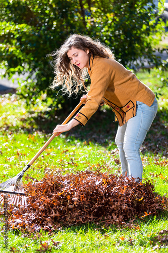 Young woman girl working in backyard raking collecting of dry autumn foliage oak Canvas-taulu