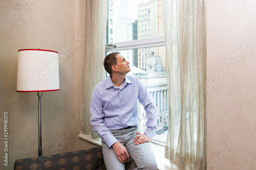 Young man businessman sitting at window in hotel room looking up through glass dreaming of NYC city by lamp on windowsill