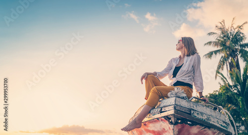 Foto op Aluminium Zanzibar Girl in a white shirt sitting on an old deryavyanoy boat on the beach and watching the sunset, relax in the tropics, vacation and travel concept