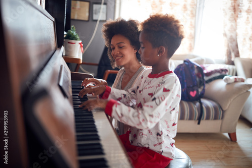 family at Christmas play music on piano.Mother with child girl on Christmas play music