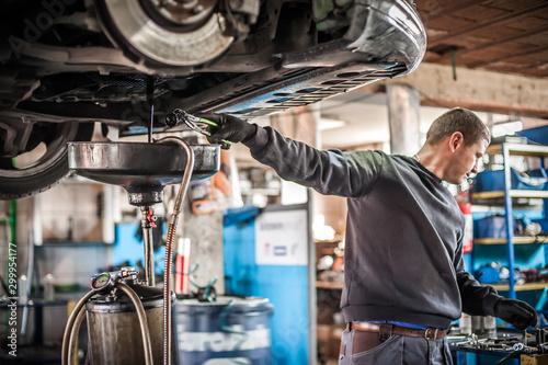 Mechanic discharges motor oil from engine tank under the car Tapéta, Fotótapéta