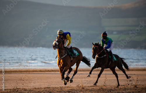 Two race hoses and jockeys racing on the beach at sunset, horse racing on the west coast of Ireland