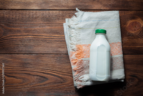 Pinturas sobre lienzo  Bottle of fresh milk and kitchen towel on brown wooden table background