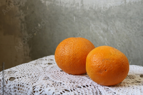 Orange two oranges on a white table cloth hand-knitted by a concrete gray wall in divorces in the loft Canvas Print