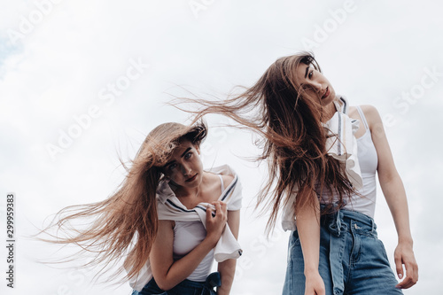 Photo  Portrait of Two Young Brunette Twins Sisters Dressed Alike in Jeans and White T-