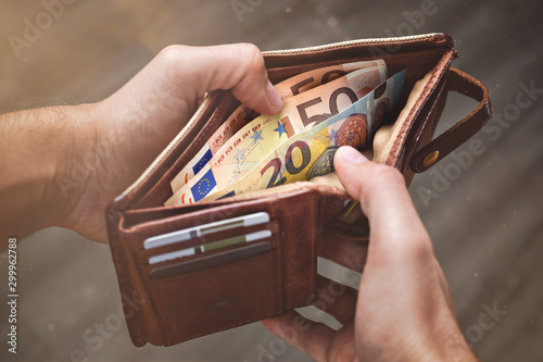 Fotomural Hands opening a leather wallet with Euro banknotes inside