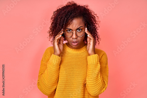 Fotografering  Shocked emotional dark haired woman keeps hands on rim of spectacles, gazes with stupefaction, receives surprising news, models against pink studio wall