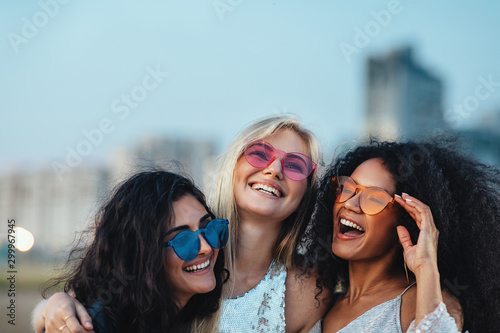 Obraz na plátne Three beautiful women with colorful sunglasses standing at evening outdoors