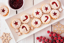 Christmas Holiday Jam Filled Cookies. Top View Table Scene Against A White Wood Background.