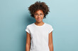 Leinwanddruck Bild - Attractive female student with curly hair, wears transparent glasses, white t shirt, stands against blue background, has calm face expression, tender smile, listens interlocutor with pleasure