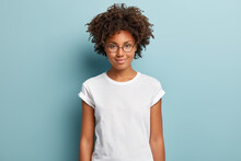 Attractive Female Student With Curly Hair, Wears Transparent Glasses, White T Shirt, Stands Against Blue Background, Has Calm Face Expression, Tender Smile, Listens Interlocutor With Pleasure