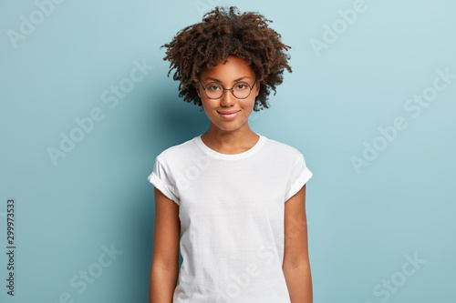Obraz Attractive female student with curly hair, wears transparent glasses, white t shirt, stands against blue background, has calm face expression, tender smile, listens interlocutor with pleasure - fototapety do salonu