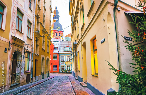 Foto Narrow street leading to St Peter church in Old Riga