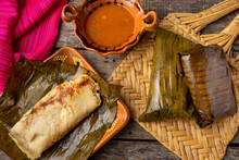 """Mexican Tamales Wrapped In Banana Leaves Also Called """"oaxaqueños"""" On Wooden Background"""