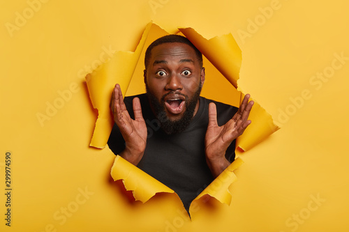 Amazed emotional Afro American man raises hands up, stares with surprised expres Fototapet
