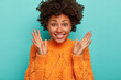 Close up shot of joyful curly woman expresses enthusiasm and joy, keeps palms raised, smiles broadly, wears bright winter sweater, enjoys amusing night with friends, isolated on blue background