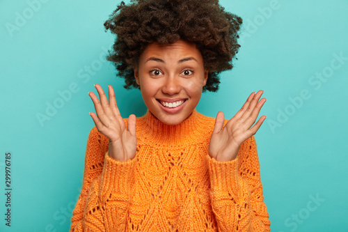 Pinturas sobre lienzo  Close up shot of joyful curly woman expresses enthusiasm and joy, keeps palms ra