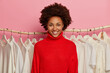canvas print picture - Happy dark skinned female stylist with Afro hairstyle, smiles broadly, wears knitted red sweater, stands near rack with hangers. Friendly shop assistant in fashion store, white clothes in background