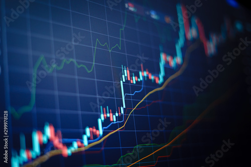Obraz Closeup financial chart with uptrend line candlestick graph in stock market on blue color monitor background - fototapety do salonu