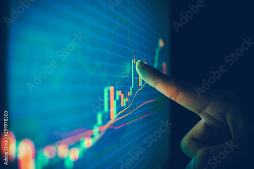 Fotografía  Closeup hand pointing finger on blue color monitor to analyze stock market graph