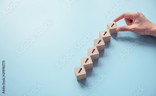 Fototapeta Business concept growth success process, Close up Woman hand arranging wood block stacking as step stair on paper blue background, copy space. obraz na płótnie