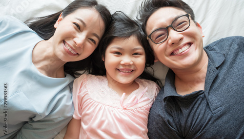 Fényképezés  portrait of happy Asian family lying on bed and looking up and holding hands