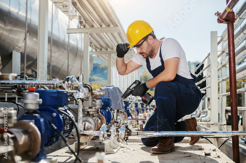 Fotomural  Handsome caucasian worker in overall and helmet on head crouching and using drill while crouching