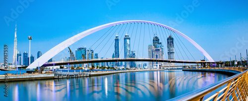 colorful sunset over Dubai Downtown skyscrapers and the newly built Tolerance bridge as viewed from the Dubai water canal - 299987559