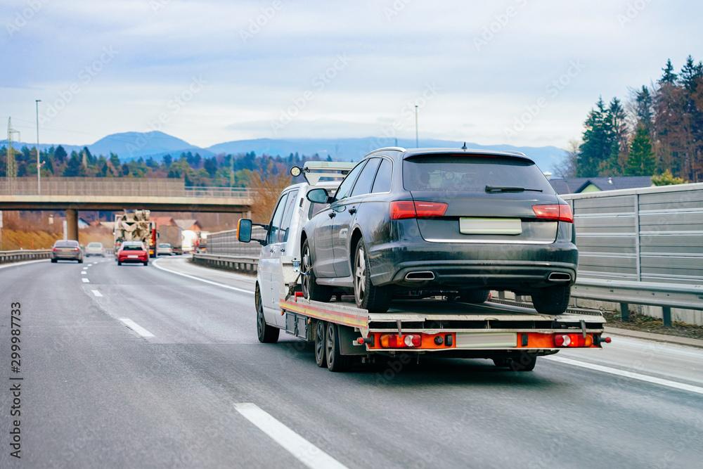 Fototapeta Tow truck with car on warranty in road