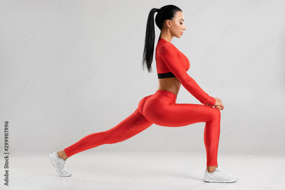 Fototapety, obrazy: Fitness woman doing lunges exercises for leg muscle workout training. Active girl doing front forward one leg step lunge exercise, on the gray background