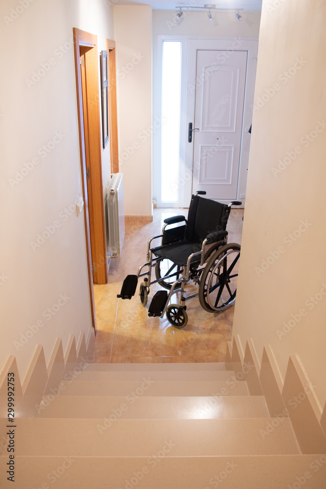 Fototapety, obrazy: A wheelchair in front of a staircase in a house