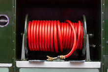 Red Fire Hose Coiled Up On An Old Fire Engine, The Green Godded