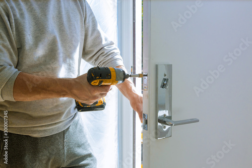 Installation with a lock in the door leaf using an drill screwdriver Canvas Print