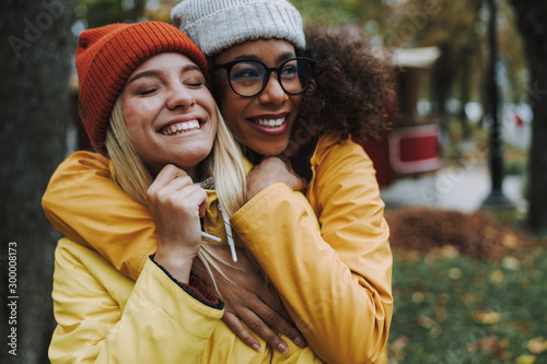 Two young women hugging and smiling cheerful Canvas