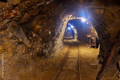 Mining tunnel underground with lights and rails