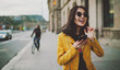 Cheerful asian student girl wearing modern sunglasses laughing at friends' photos in social media by a mobile phone. Happy model look woman in casual outfit checking blog comments via smartphone.