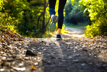 Legs of female runner in motion on a trail in the nature.
