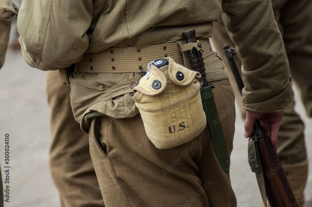 Fototapety, obrazy: Closeup of american soldier in uniform with water gourd during the world war two reconstitution for the 75th anniversary of the liberation of Alsace in France